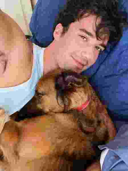 O cachorro Caju é abraçado pelo dono Lurryan - reprodução/Instagram