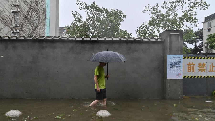25.jul.2021 - Homem caminha em uma rua inundada em um bairro em Ningbo, província de Zhejiang, leste da China - Hector Retamal/AFP