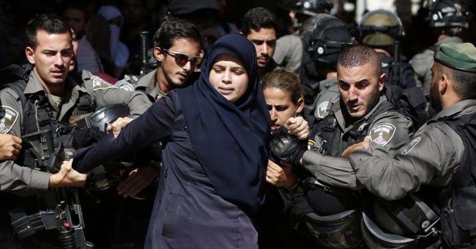 26.jul.2015 - Forças de segurança de Israel prendem mulher palestina durante confrontos entre palestinos e policiais israelenses em Jerusalém. O choque foi provocado após a tentativa de judeus ultranacionalistas de rezar no Monte do Templo. A polícia israelense penetrou alguns metros na mesquita de Al-Aqsa, dando início ao conflito