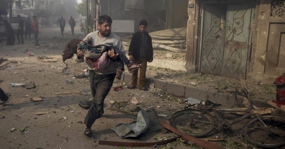 7.nov.2015 - Um homem carrega uma criança nos braços em busca de socorro após bombardeio aéreo neste sábado, em Douma, na Síria. Ativistas afirmam que o ataque foi feito por forças leais ao presidente sírio, Bashar al-Assad