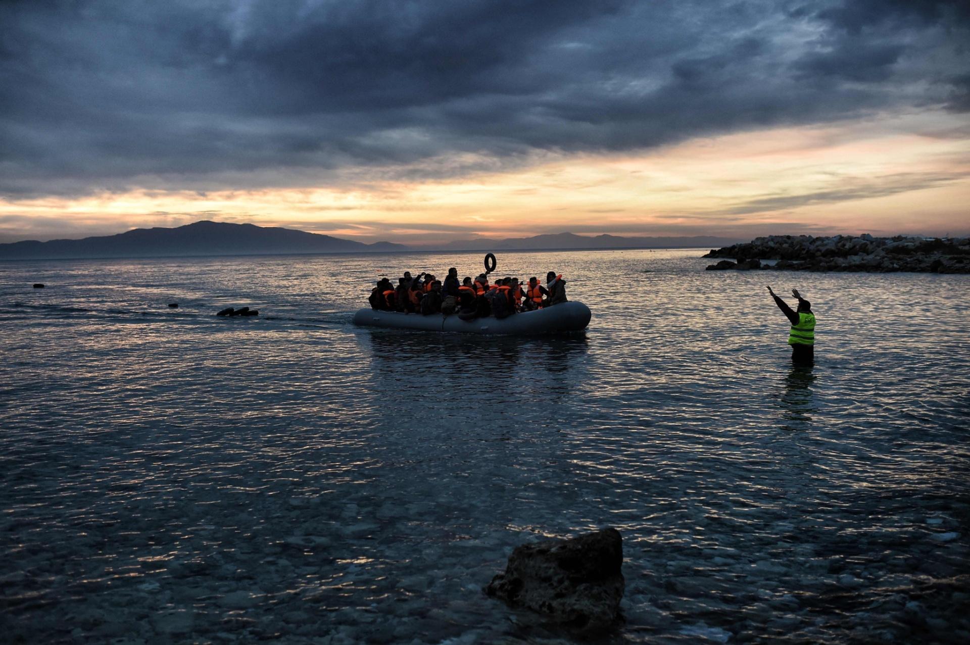 17.fev.2016 - Membro de equipe de resgate acena para bote inflável lotado de imigrantes no norte da ilha de Lesbos, na Grécia, após a embarcação cruzar o mar Egeu, saídos da Turquia