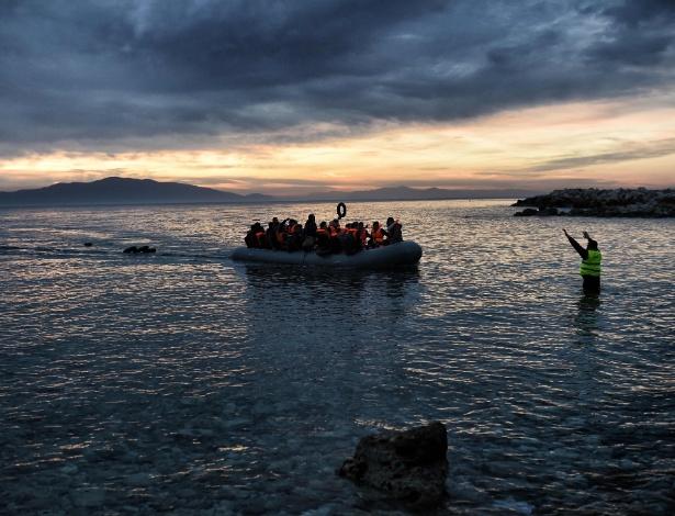 17.fev.2016 - Integrante de equipe de resgate acena para bote inflável lotado de imigrantes no norte da ilha de Lesbos, na Grécia