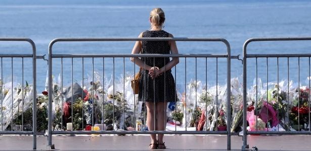 Mulher observa memorial improvisado em homenagem às vítimas do ataque com caminhão em Nice, na França
