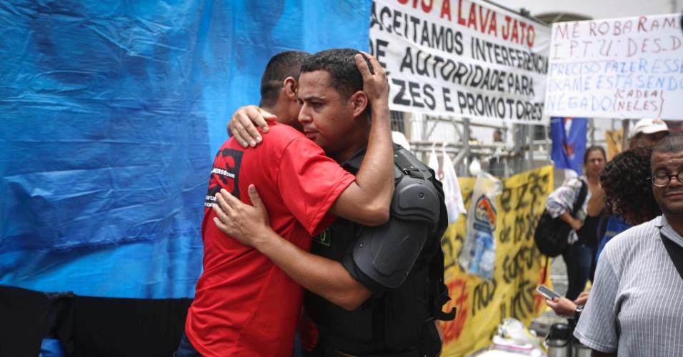 13.dez.2016 - Policial militar abraça manifestante em frente ao Palácio Tiradentes, sede do Legislativo do Rio, onde deputados estaduais votam o pacote de medidas anticrise sugerido pelo governo do Estado