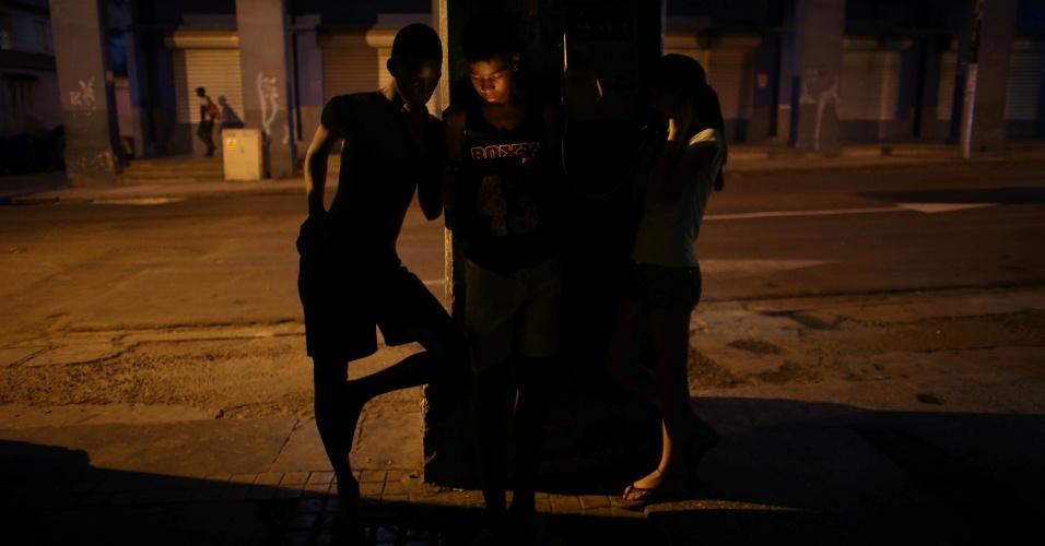 Jovens usam celular para conectarem-se à internet, em Havana, enquanto garota utiliza telefone público