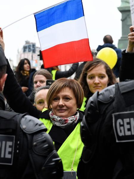 Mulher segura bandeira da França em frente a policiais franceses durante protesto - Bertrand Guay/AFP