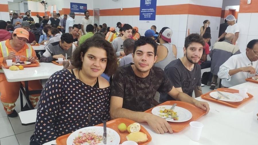 Isis, 22, ao lado do amigo Kevin, 28: sem renda, ela junta as moedas para almoçar todos os dias a R$ 1 - BBC News Brasil
