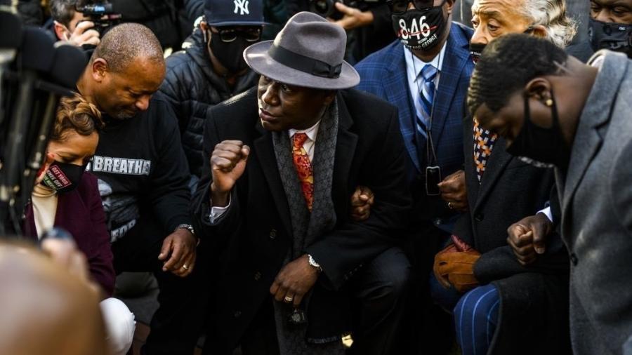 O advogado Ben Crump se ajoelha com familiares de George Floyd e manifestantes durante 8 minutos e 46 segundos, o tempo em que o policial Derek Chauvin passou pressionando a garganta do homem negro assassinado em 2020 - Divulgação