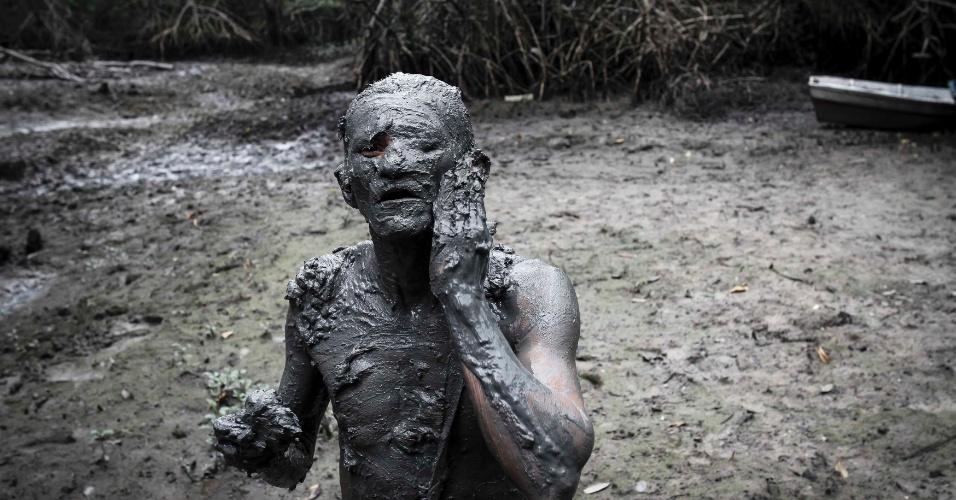7.fev.2016 - Folião se 'veste' com o abadá ecológico, feito de lama do mangue, no bloco Pretinhos do Mangue, no município de Curuca, nordeste do Pará