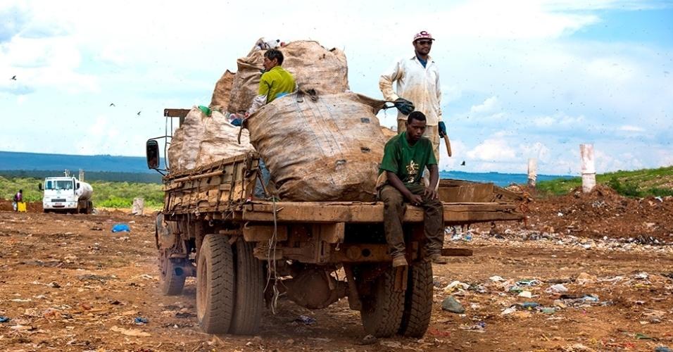 12.mar.2016 - Os catadores trabalham sem equipamento de proteção e correm dos caminhões e tratores para não serem atropelados. Acima, catadores pegam carona de forma irregular em um caminhão de lixo