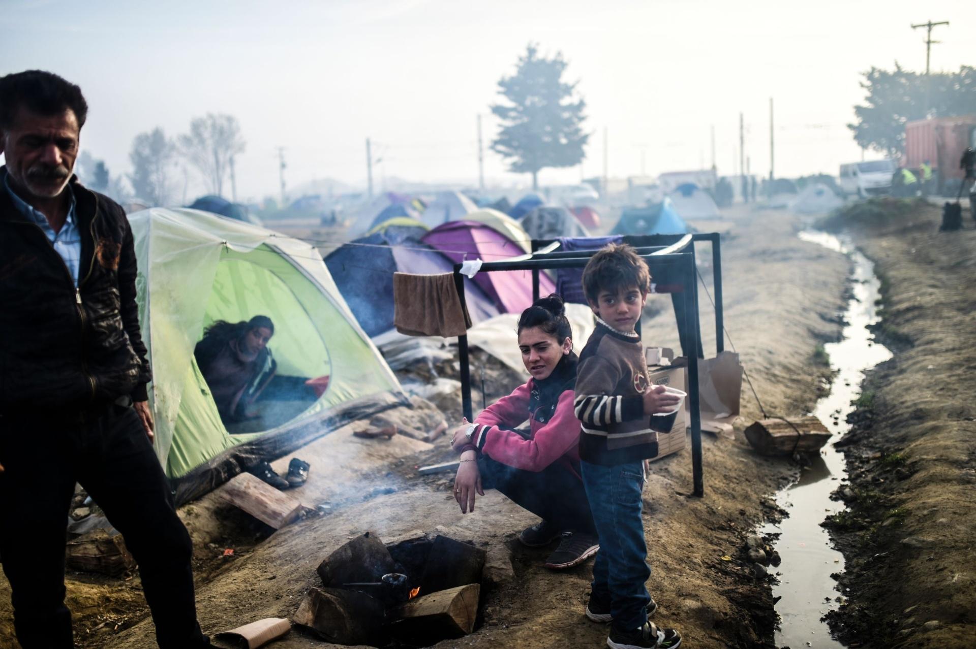 1º.abr.2016 - Grupo de refugiados amanhece em acampamento improvisado na fronteira da Grécia com a Macedônia, perto da aldeia de Idomeni, onde milhares de imigrantes estão retidos pelo bloqueio das fronteiras dos países balcânicos. O chefe da ONU, Ban Ki-moon, pediu na quarta-feira maiores esforços para enfrentar a crise de refugiados da Síria