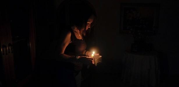 Venezuelana segura vela em casa; governo revoga racionamento