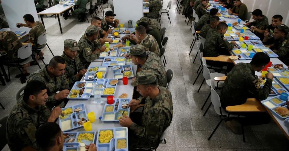 4.jul.2016 - Oficiais palestinos das forças nacionais de segurança comem o iftar enquanto quebram o jejum diário do mês sagrado do Ramadã, no refeitório da base em Jericó, na Cisjordânia
