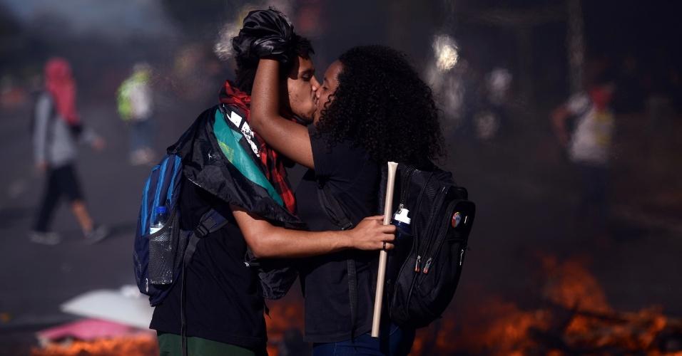 24.mai.2017 - Casal se beija durante conflito com policiais no Eixo Monumental, em frente do Congresso Nacional, em Brasília