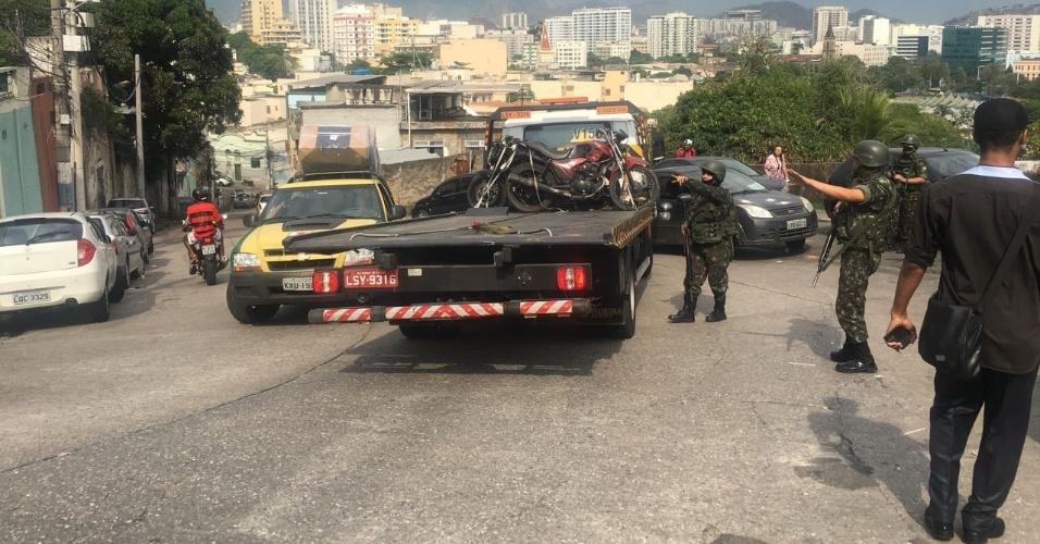 27.out.2017 - Militares que atuam no cerco ao São Carlos dá ordem de parada a veículo de carga que descia a favela. As tropas estão posicionadas nas principais rotas de acesso à comunidade. Carros de passeio e mototaxistas também estão sendo parados e revistados