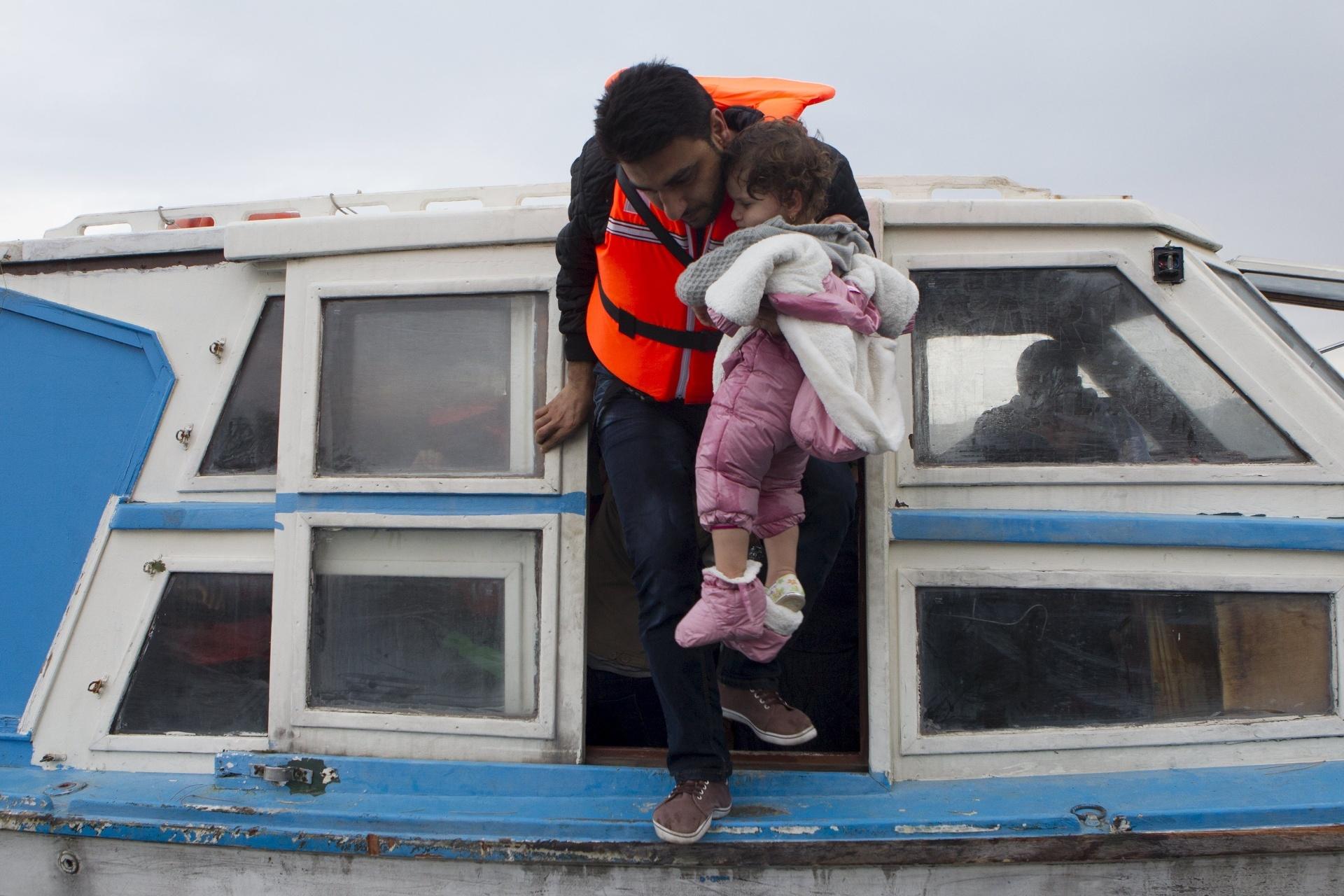 29.set.2015 - Refugiado sírio carrega criança ao chegar á ilha de Lesbo, na Grécia, após atravessar o mar Egeu a partir da Turquia