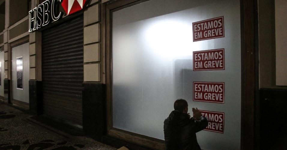6.out.2015 - Sindicalista faz colagem de adesivos da greve na fachada da agência bancária, em Curitiba (PR). Bancários de todo o país iniciam nesta terça-feira paralisação por tempo indeterminado