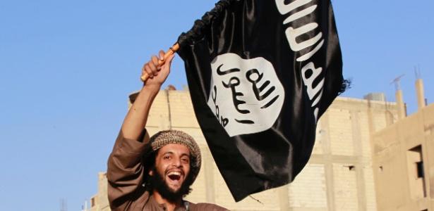 Militantes islâmico balança bandeira do Estado Islâmico em Raqqa, na Síria