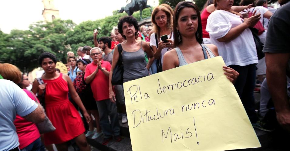"""18.mar.2016 - Em concentração na praça 15, no centro do Rio de Janeiro, uma jovem segura um cartaz escrito """"Pela democracia, ditadura nunca mais!? durante ato a favor da democracia e contra o impeachment da presidente Dilma Rousseff"""