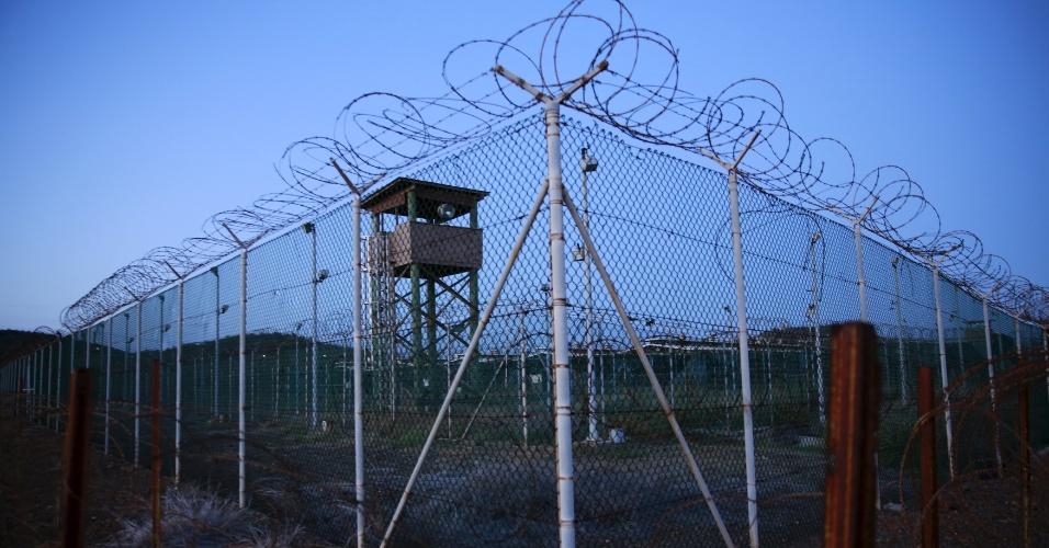 """28.mar.2016 - """"Estou trabalhando há sete anos para fechar essa prisão. Não quero passar isso para o próximo presidente. Vamos fazer o que é certo para o país. Vamos fechar esse capítulo"""", disse Obama no final de fevereiro, quando apresentou um plano para fechar a prisão na base militar. Na foto feita dia 21 de março, arrame-farpado cerca uma torre de guarda dentro do Campo Delta da Força Tarefa Conjunta de Guantánamo"""