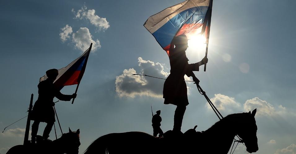 29.ago.2016 - Cavaleiros seguram a bandeira nacional russa em Moscovo, durante comemorações do Dia da Bandeira Nacional, na Rússia