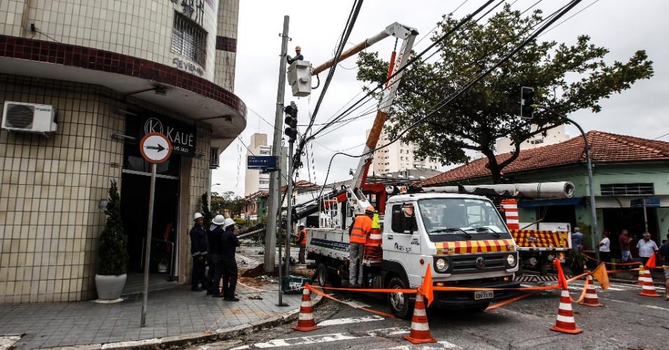 21.out.2016 - Funcionários trabalham para remover uma árvore que caiu com a forte chuva desta quinta-feira (20), na rua Albion, na Lapa, zona oeste de São Paulo