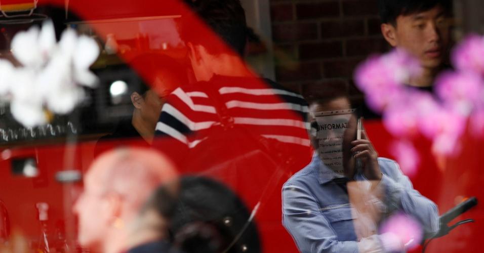 1.dez.2016 - Homem é refletido em janela enquanto usa seu telefone celular em Shoreditch, Londres, no Reino Unido