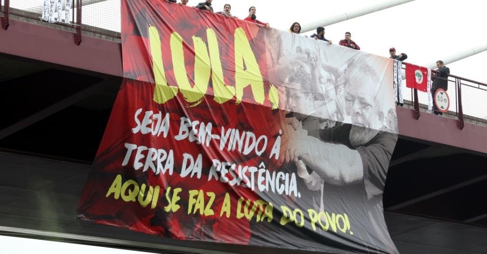 Manifestantes contra e a favor de Lula exibem faixas e cartazes no caminho da comitiva do ex-presidente