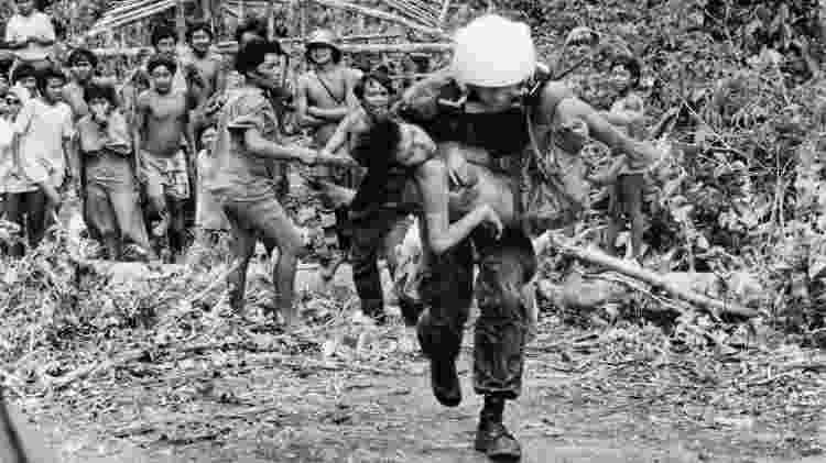 Piloto de helicóptero da Força Aérea Brasileira (FAB) remove, da maloca do Homoxi para o posto médico de Surucucus, Yanomami vítima da invasão garimpeira na Terra Indígena Yanomami, Roraima - Charles Vincent / ISA / Arquivo 1990 - Charles Vincent / ISA / Arquivo 1990