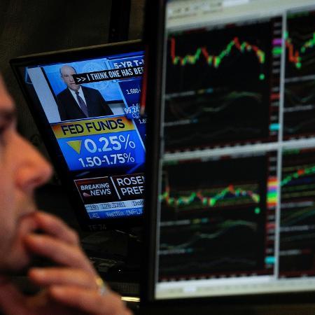 Operador na Bolsa de Valores de Nova York durante anúncio da taxa de juros norte-americana pelo Fed - BRENDAN MCDERMID