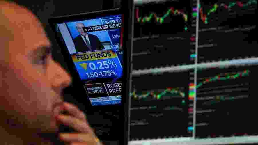Operador na Bolsa de Valores de Nova York durante anúncio do mais recente corte da taxa de juros norte-americana pelo Fed - BRENDAN MCDERMID