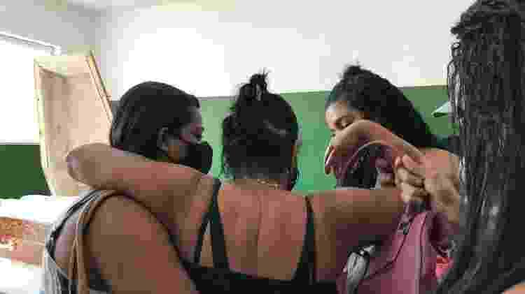 2.dez.2020 - Marlene Alves Frauzino (de costas) é consolada pelas filhas em enterro do seu filho, o morador de rua Carlos Eduardo Pires de Magalhães, que morreu dentro de uma padaria na zona sul do Rio de Janeiro - Herculano Barreto Filho/UOL - Herculano Barreto Filho/UOL