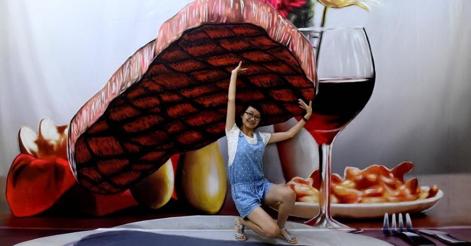 22.jul.2015 - Visitante posa para foto em um museu de arte da ilusão em Zhengzhou, na província de Henan, no centro da China
