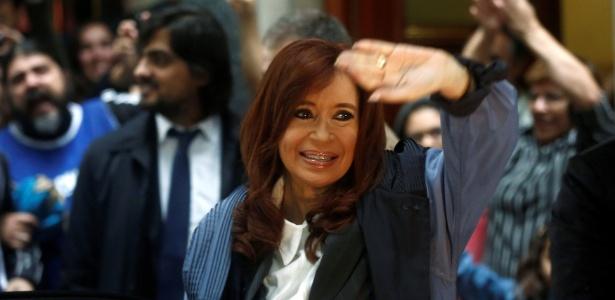 Sob chuva, a ex-presidente argentina Cristina Kirchner acena para simpatizantes ao deixar sua casa e se dirigir para corte, em Buenos Aires