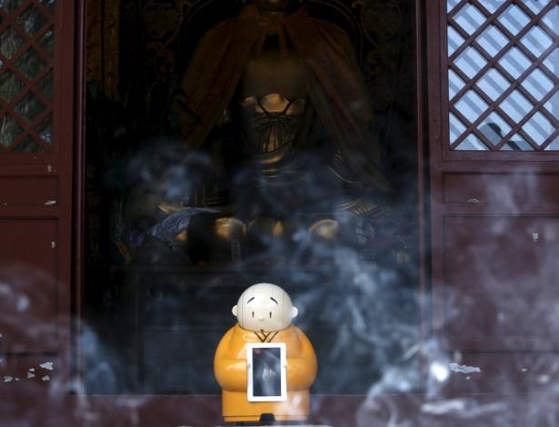 O robô Xian'er fica posicionado em frente ao templo, envolto em fumaça de incenso