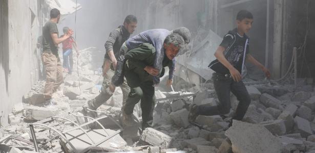 Sírios evacuam edifícios destruídos após ataques aéreos em Aleppo