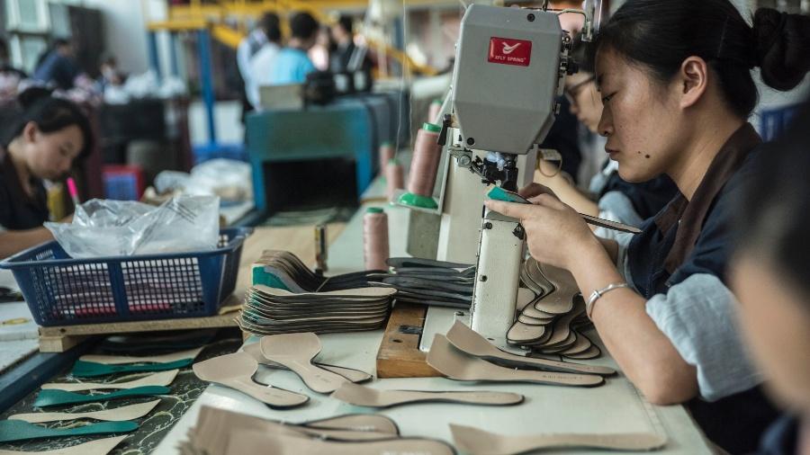 Mulher trabalha na fábrica de sapatos Huajian International, que faz sapatos para Ivanka Trump e outros designers, em Dongguan, na China  - GILLES SABRIÈ/NYT