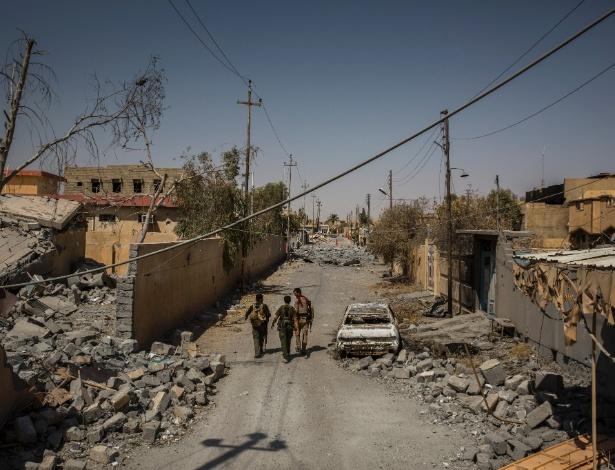 Soldados da milícia Shia andam em rua danificada depois que os combatentes do Estado Islâmico deixaram a área, em Tal Afar, no Iraque