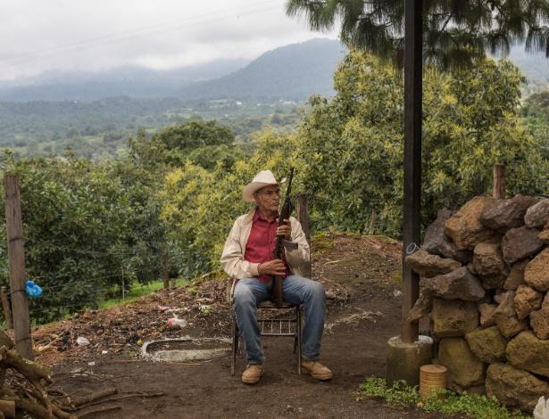 Miliciano guarda local próximo à entrada de Tancítaro, no México