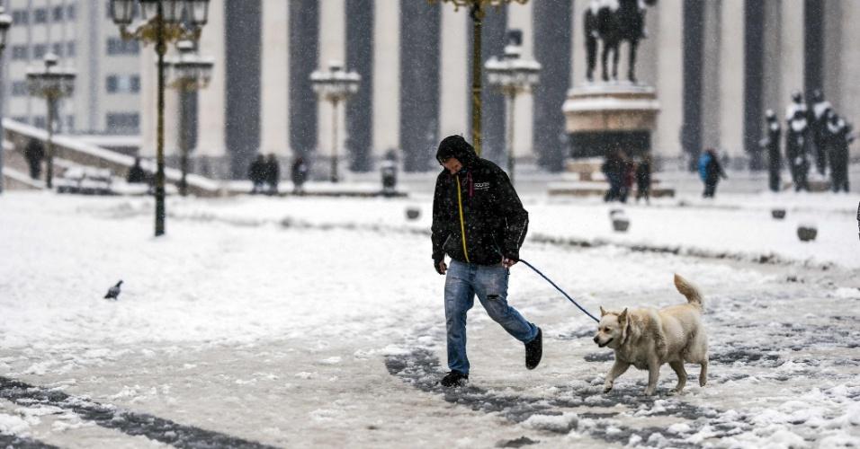 26.fev.2018 - Homem passeia com cachorro na praça principal de Escópia, capital da Macedônia, durante uma nevasca