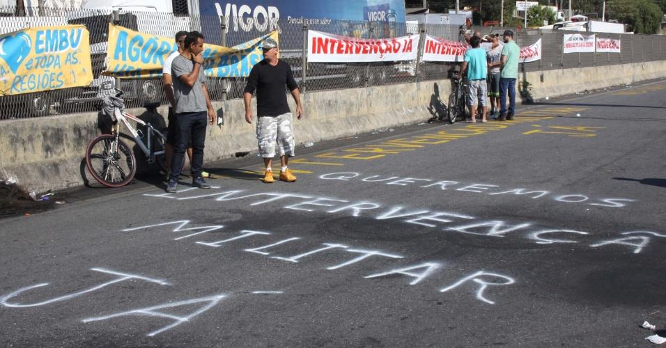 27.mai.2018 - No ponto em que caminhoneiros grevistas bloqueiam a rodovia Régis Bittencourt, na Grande São Paulo, manifestantes usam cartazes e pintam frases no asfalto para pedir intervenção militar no país