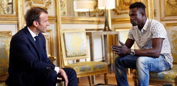 28.mai.2018 - Emmanuel Macron e malinês Mamoudou Gassama, que escalou um prédio para salvar uma criança em Paris
