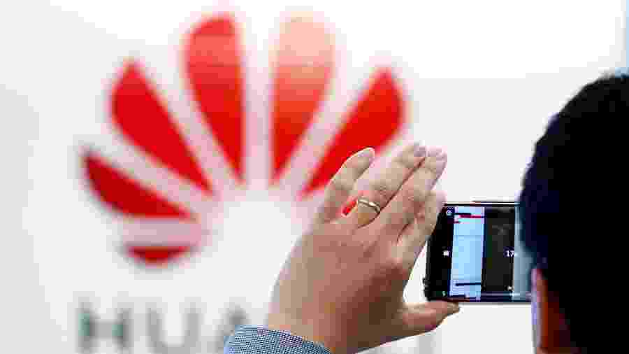 Homem tira foro do logotipo da Huawei estampado no Centro de Cibersegurança da empresa em Bruxelas - François Lenoir/Reuters