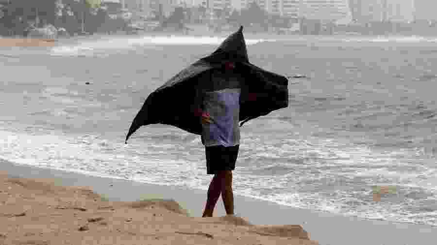 18.set.2019 - Homem se protege da chuva durante passagem do Lorena, em Acapulco, no México - Javier Verdin - 18.set.2019/Reuters