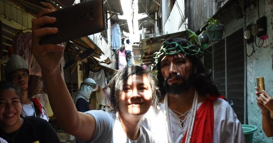 24.mar.2016 - Com o celular, mulher registra uma selfie ao lado de um ator caracterizado como Jesus Cristo durante celebração da Semana Santa em Manila, capital das Filipinas
