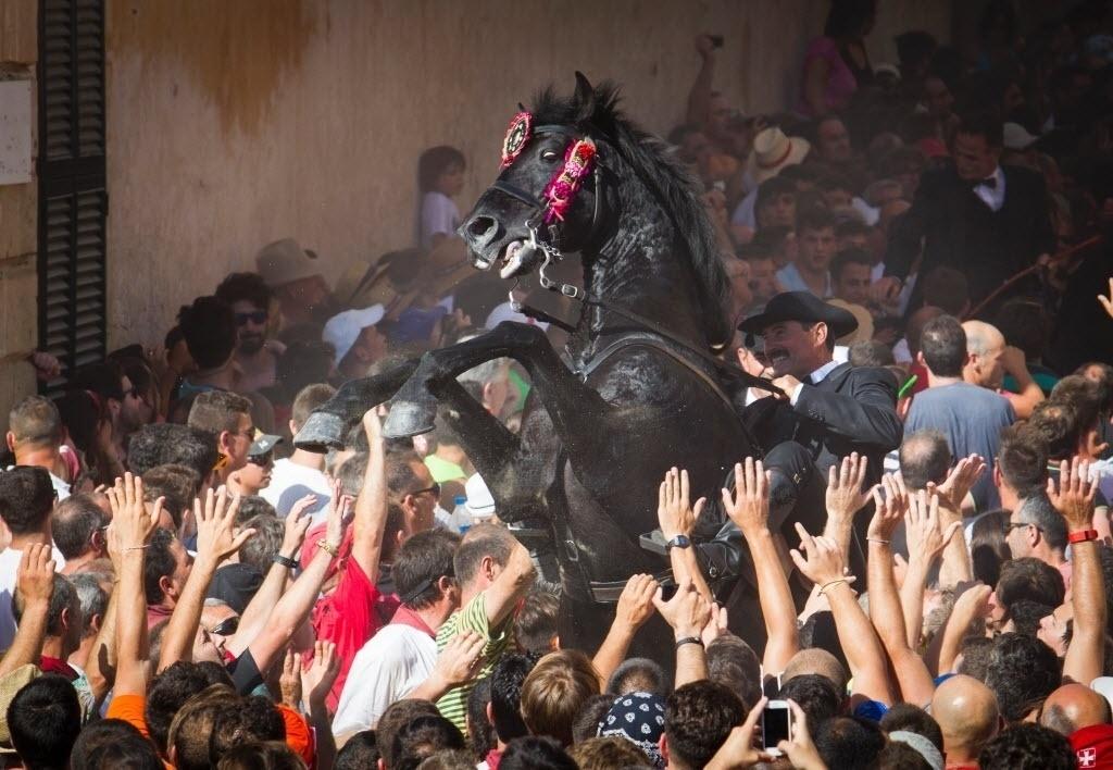 23.jun.2016 - Um cavalo se exibe entre uma multidão na tradicional festa de São João da cidade de Ciutadella, na Espanha. Durante o evento, realizado anualmente no local, os cavalos participam de corridas e se apresentam empinados as patas pelas ruas