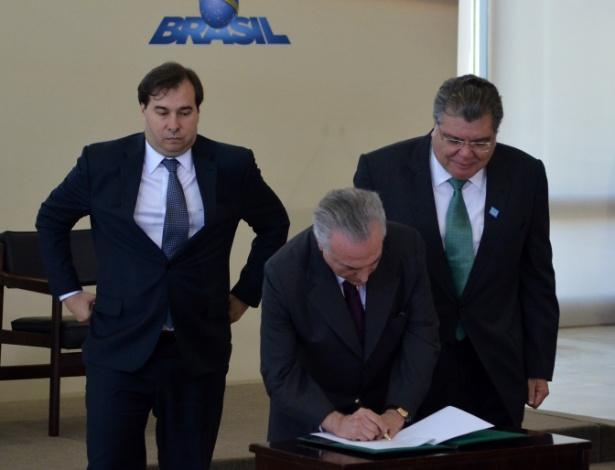Acompanhado do presidente da Câmara dos Deputados, Rodirgo Maia (esq.), e do ministro do Meio Ambiente, José Sarney Filho (dir.), o presidente Michel Temer ratifica o acordo do Clima de Paris