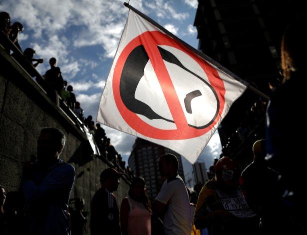 Manifestante seguram bandeira com desenho do presidente Nicolás Maduro durante protesto em Caracas, na Venezuela