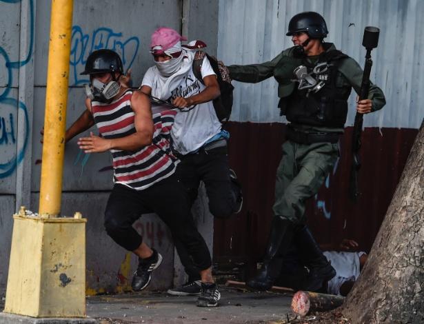 27.jul.2017 - Membro da Guarda Nacional tenta deter manifestantes durante confrontos em Caracas, Venezuela