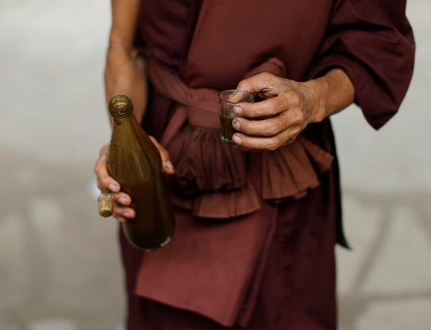Monge budista segura copo e garrafa com bebida que desintoxica viciados em drogas no templo Tham Krabok, em Saraburi, na Tailândia - Jorge Silva/Reuters